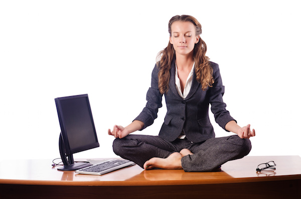 business woman meditating sitting on a desk beside a computer