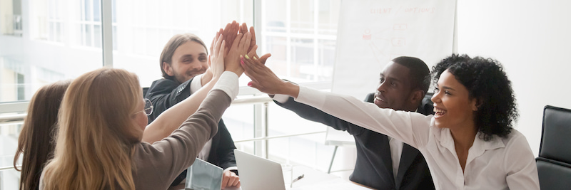 business-people-sitting-at-desk-boardroom-celebrating-success-giving-high-five-feels-happy-excited-team-spirit-unity-concept